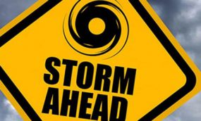 A yellow caution sign on a road that says STORM AHEAD and has an icon of a hurricane.