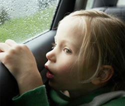 Photo of a young girl looking out a car window