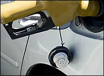 Photo of gasoline nozzle in car tank.