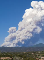 Photo of smoke rising from a mountian landscape.