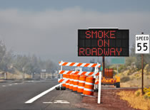 Photo of a road sign warning drivers of smoke on the highway.