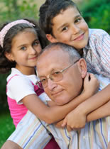 Photo of an elderly man being hugged by two children.