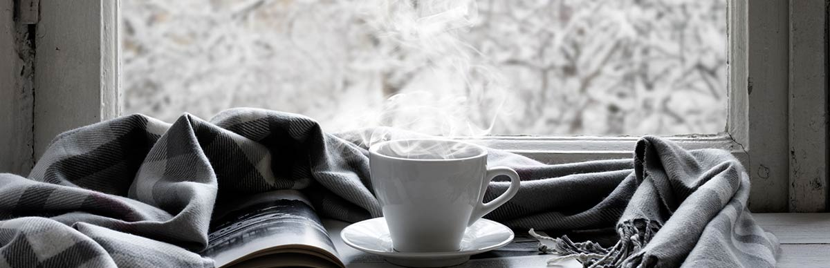 A book, a grey and white scarf, and white mug full of a steamy, hot drink are placed on a table facing a window that is showing a snowy landscape outside.