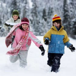 Three young children running through the snow wearing winter clothing