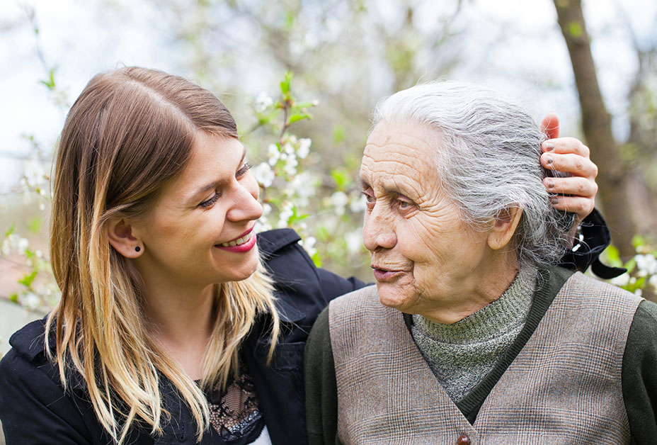 Adult woman stroking grandmother's hair
