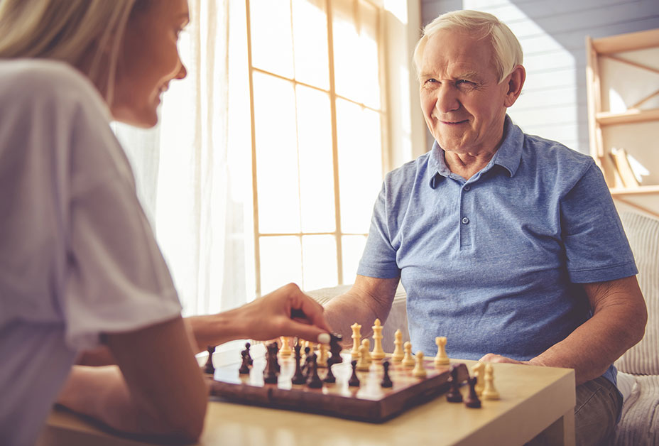 Senior man playing chess with younger woman