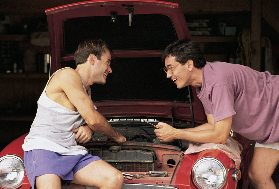 Two guys working on an old car