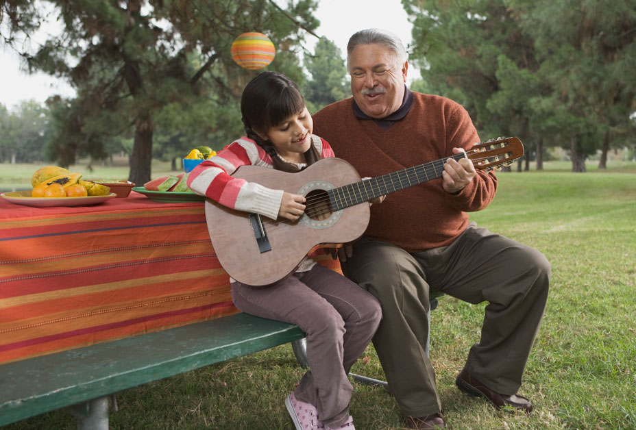 Grandfather and granddaughter playing guitar