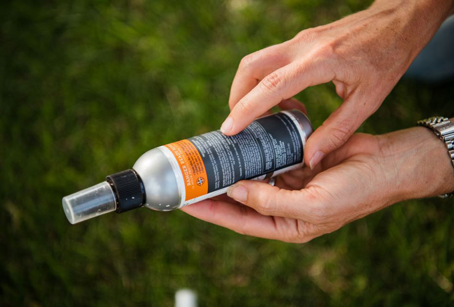 Woman spraying on insect repellent