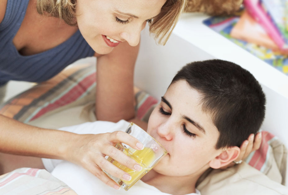 Mother giving orange juice to sick son