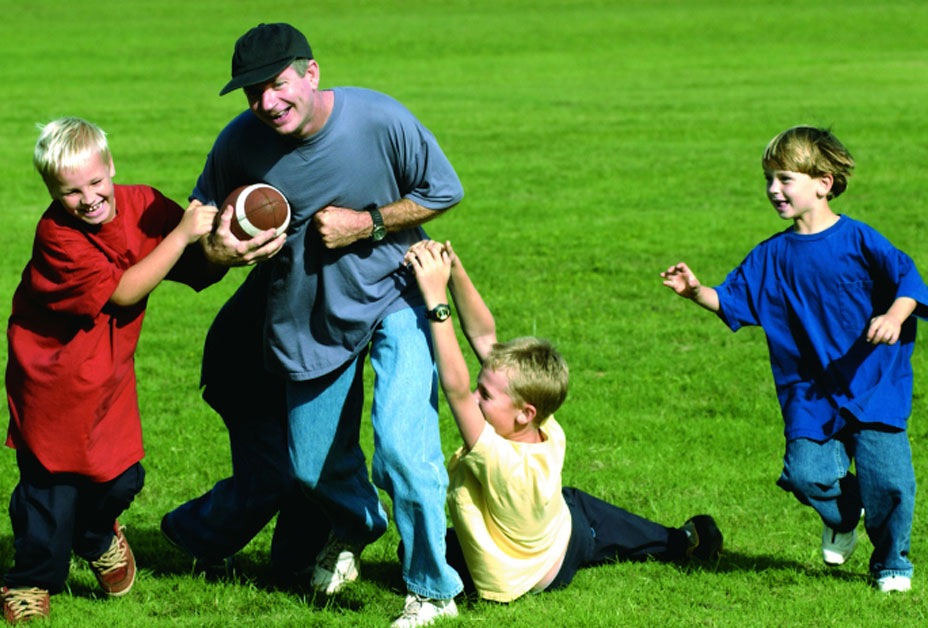 Father playing football with three boys