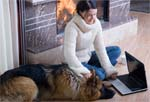Woman sitting in front of fireplace with dog and laptop