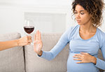 Pregnant woman declining glass of wine