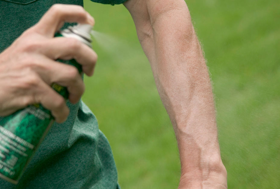 Man spraying insect repellent on arm