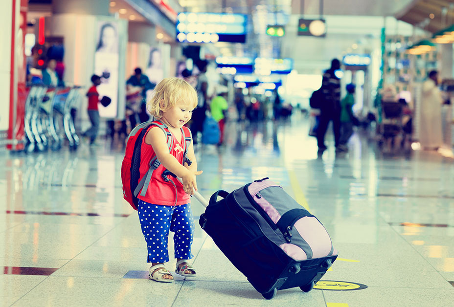 Young girl pulling suitcase through airport