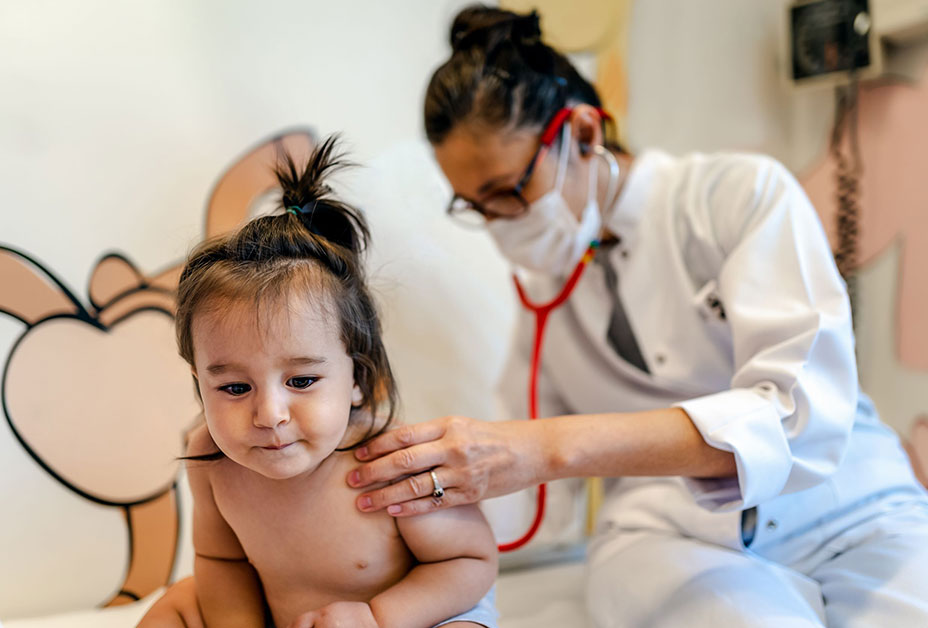 Doctor examining child on mother's lap and smiling