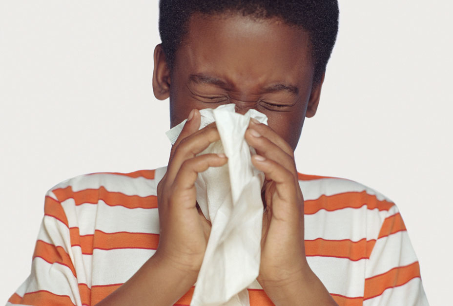Boy sneezing into tissue
