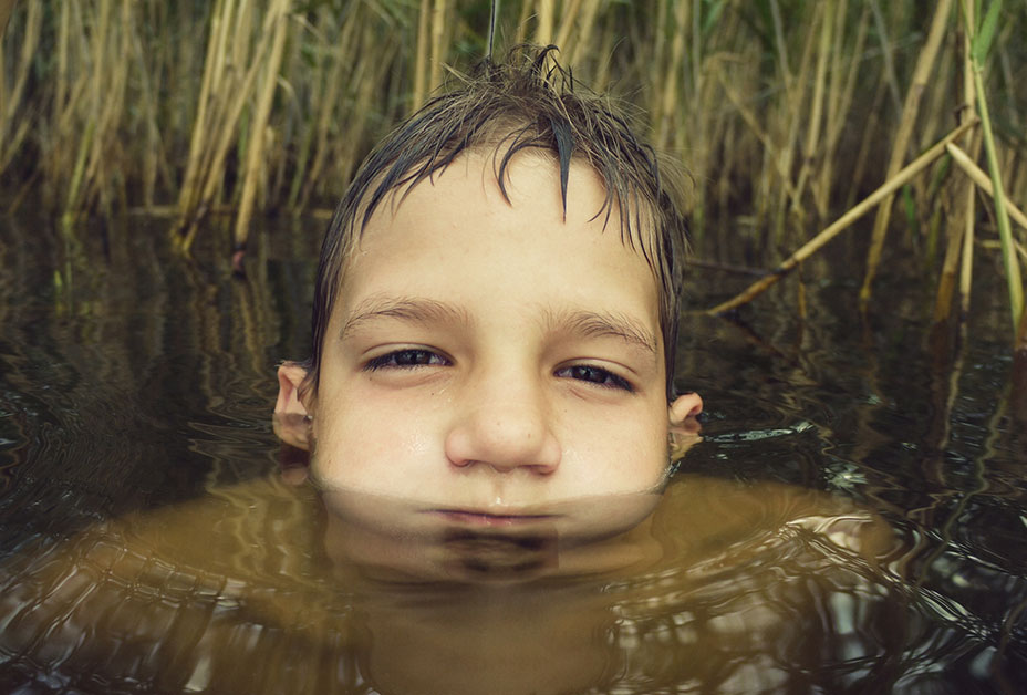Young boy submerged in water
