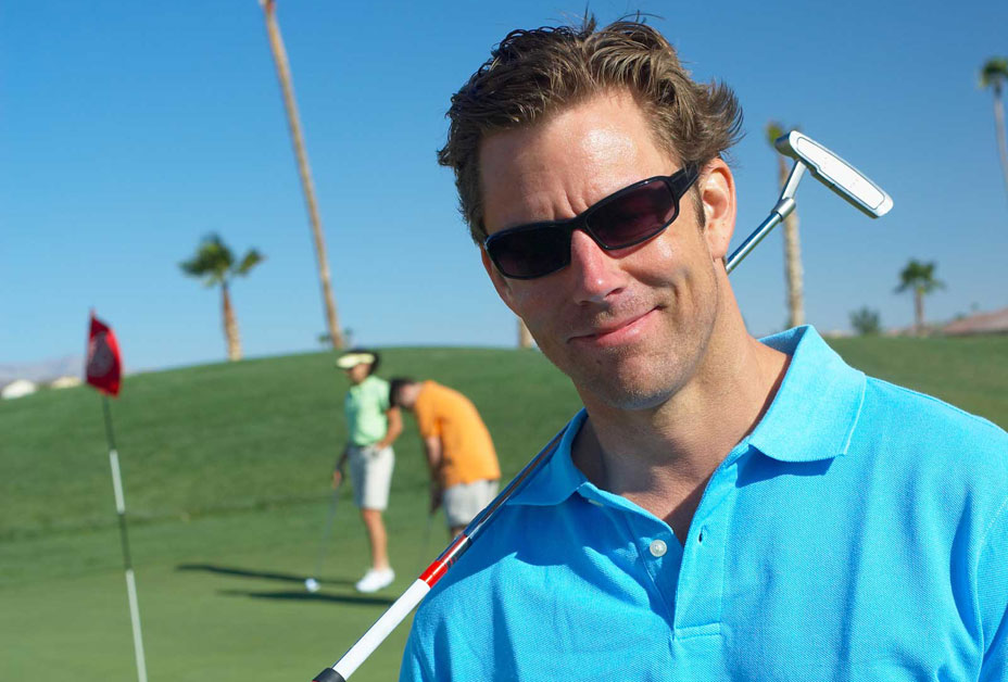 Man playing golf and wearing sunglasses
