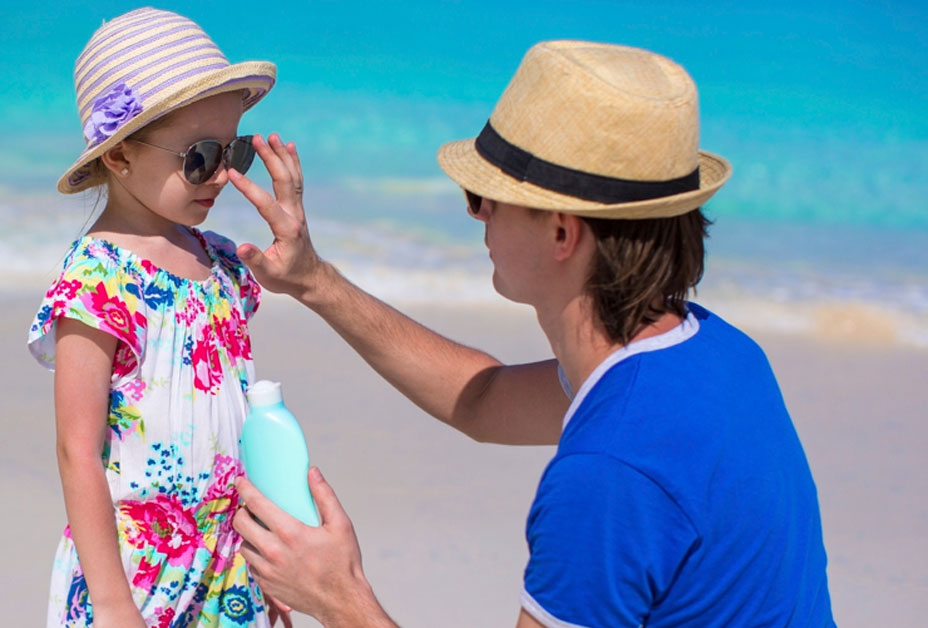 Father applying sunscreen to daughter