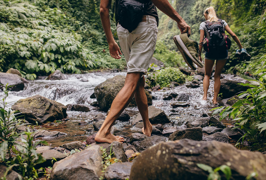 Couple hiking barefoot through stream