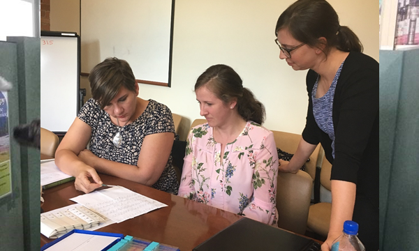 Nancy McClung, PhD, EIS Class of 2017 (right), and colleagues reviewing slides of cervical biopsy specimens before they are sent to the CDC for HPV DNA typing.