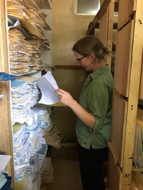 Blanche Greene-Cramer, DrPH, MPH, EIS Class of 2016, reviews a patient file during a facility visit in Liberia. Photo Credit: Endang Handzel