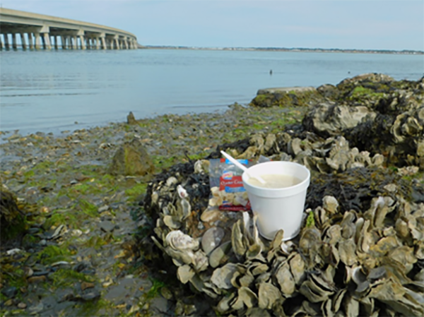 A container of clam chowder is set on a bed of oysters at Queen Sound Landing. A large outbreak of salmonellosis in early October 2017 was linked to chowder from a chili/chowder cook-off on the island. Photo courtesy of Kimberly Wright