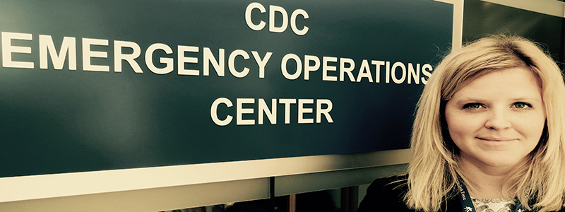 Molly Fitch standing in front of CDC Emergency Operations Center Sign