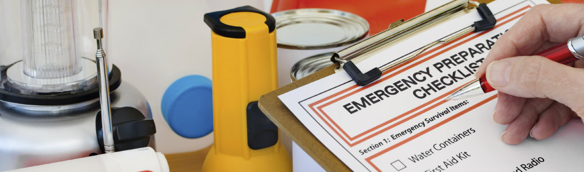emergency preparedness checklist next to emergency supplies including flashlight, lantern, cans
