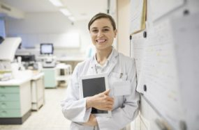 caucasian woman in labcoat standing in a hospital.
