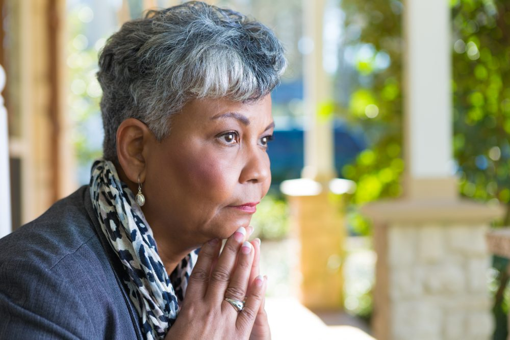 An older African American woman is outdoors staring into nature with a contemplative look on her face.