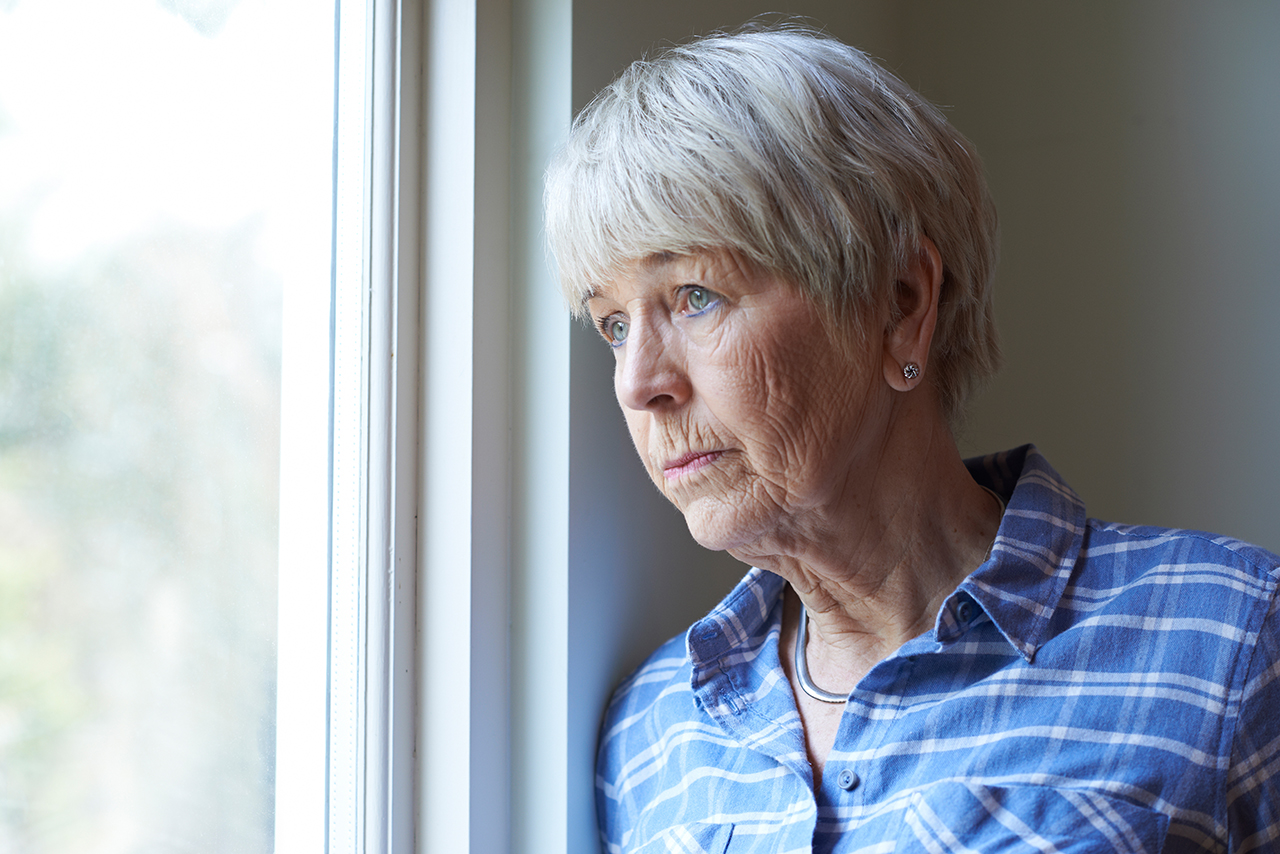 Older woman looking out of a window with a somber look.
