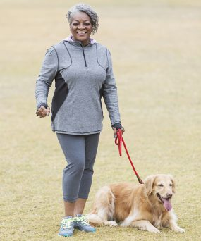 Older woman wearing exercise clothes, walking her dog.