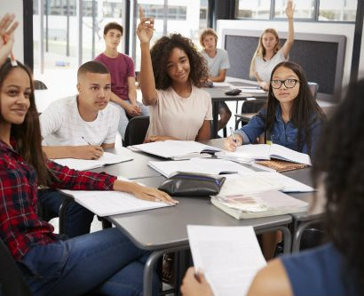 Teens in a classroom raising their hands to answer a question.