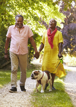 Older Black Couple Walking with a Dog and Laughing