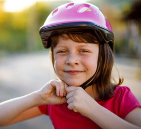 Young girl putting on bicycle helmet and smiling.