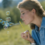 Photo: Woman blowing bubbles outdoors