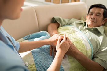 Caregiver holding the hands of an elderly man lying in bed.