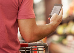Man checking smartphone while grocery shopping