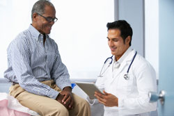 Health care provider looks at health records and talk to patient.