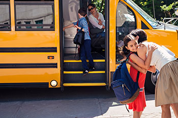 Girl hugging mother goodbye before boarding school bus