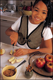 A young girl slicing fruit