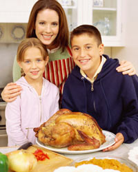 Photo: Mother and children gathered around a roasted turkey.