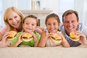 Family of four holding burgers