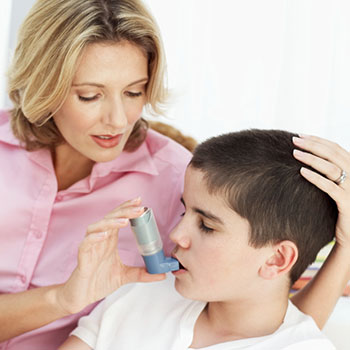 Mother giving inhaler to son