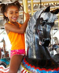 Photo: A girl riding a merry-go-round.