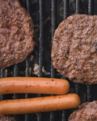 Photo: Hamburgers and hotdogs on the grill.