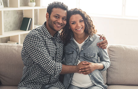 Husband and pregnant wife sitting on couch and hugging