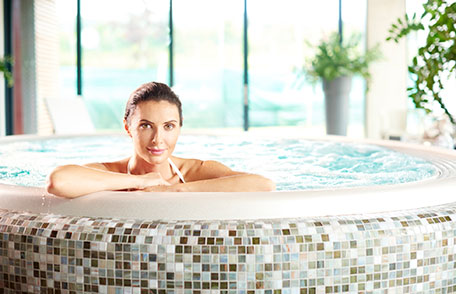 Woman in hot tub. Water in hot tubs can spread germs.